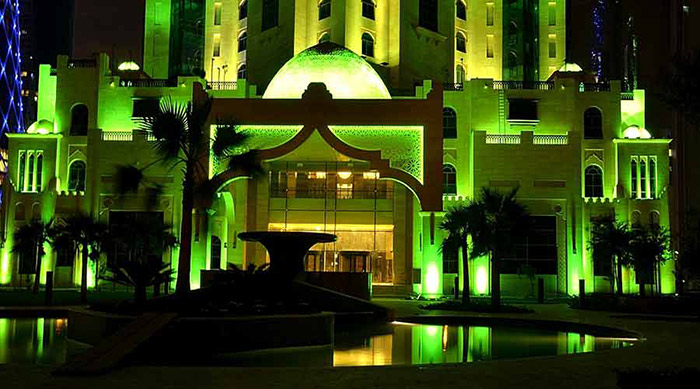 The façade of Al Jassimiya tower illuminated with Philips green lighting