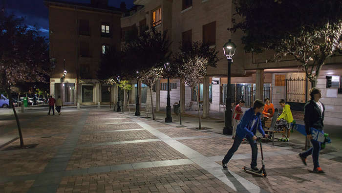 Children are playing in a square in the night under Philips lighting