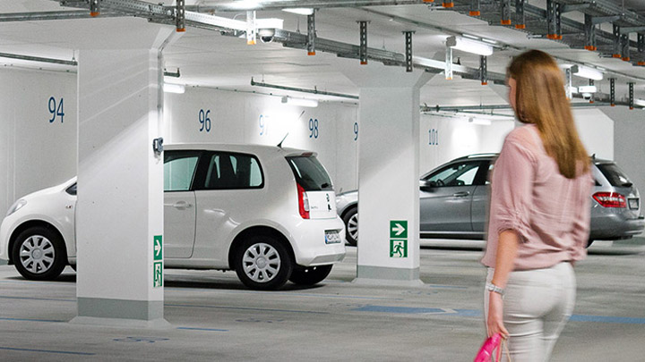 Woman walks to parked car in bright and sustainable green parking garage